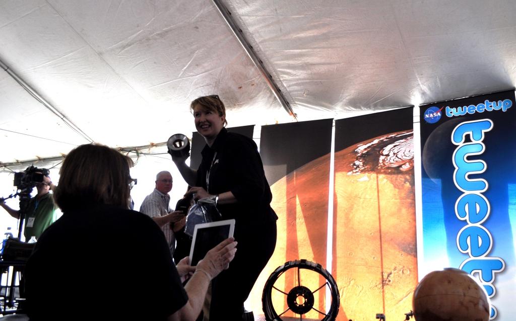 Stephanie Smith, of JPL, Displays Mars Rover Wheels, NASA Tweetup, Kennedy Space Center, Fla., Nov. 25, 2011